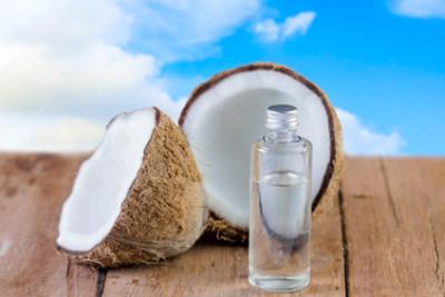 Kokosöl und Kokosnüsse auf einem braunen Holztisch