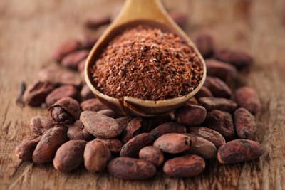 Superfood Liste - Kakaobohnen und Kakaopulver auf einem Holzlöffel